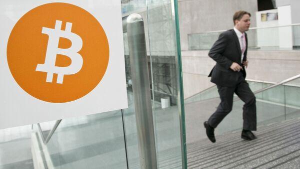 Mężczyzna mijający logotyp Bitcoin - Sputnik Polska