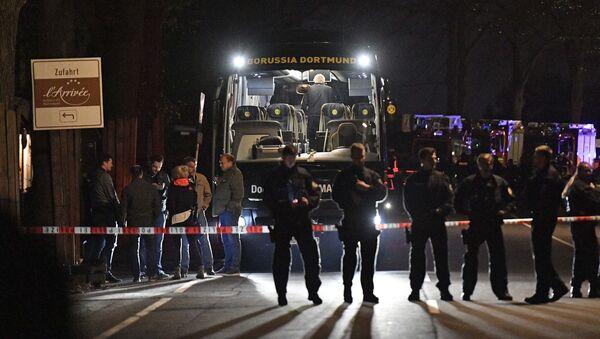 Policja obok autokaru drużyny piłkarskiej Borussia uszkodzonego w wyniku wybuchu w Dortmundzie - Sputnik Polska