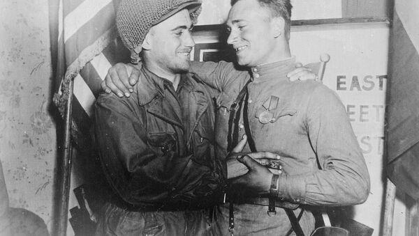 Podporucznik William Robertson z US Army oraz porucznik Aleksander Sylwaszko z Armii Czerwonej cieszący się ze spotkania się nawzajem, stojący naprzeciw napisu East Meets West, podczas spotkania armii amerykańskiej z armią radziecką w pobliżu Torgau, 27 kwietnia 1945 roku - Sputnik Polska