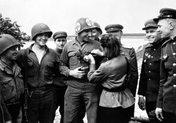 Pielęgniarka Lubow Kaziczenko ozdabia mundur amerykańskiego żołnierza Carla Robinsona kwiatami - Sputnik Polska