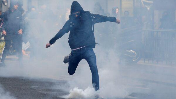 Uczeń kopie spray z gazem łzawiązym w czasie akcji protestu przeciwko Marine Le Pen i Emmanuelowi Macronowi w Paryżu - Sputnik Polska