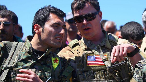 Członek kurdyjskiej Ludowej Jednostki Samoobrony i oficer USA w Syrii - Sputnik Polska