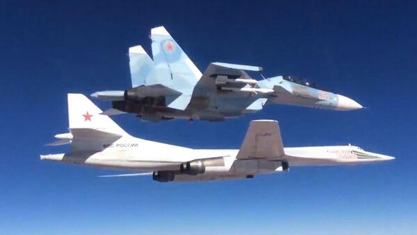 Myśliwiec Su-30SM eskortuje rosyjski odrzutowy ponaddźwiękowy bombowiec strategiczny Tu-160 - Sputnik Polska