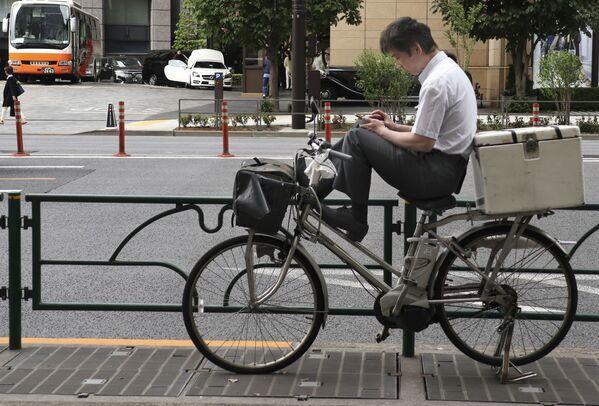 Человек с мобильным телефоном на велосипеде в торговом районе Токио - Sputnik Polska
