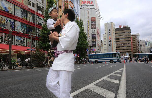 Молодой отец с маленьким ребенком на руках в Токио - Sputnik Polska
