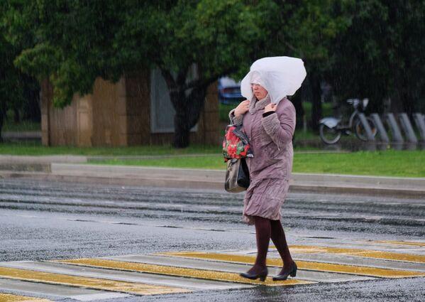 Kobieta idzie po ulicy Moskwy podczas ulewy. - Sputnik Polska