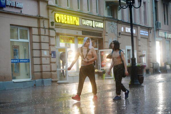 Chłopaki podczas ulewy przy Starym Arbacie w Moskwie. - Sputnik Polska