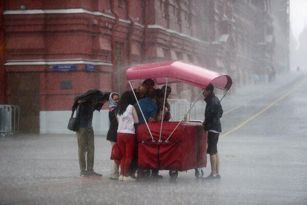 Przechodnie podczas ulewy przy Placu Czerwonym w Moskwie. - Sputnik Polska
