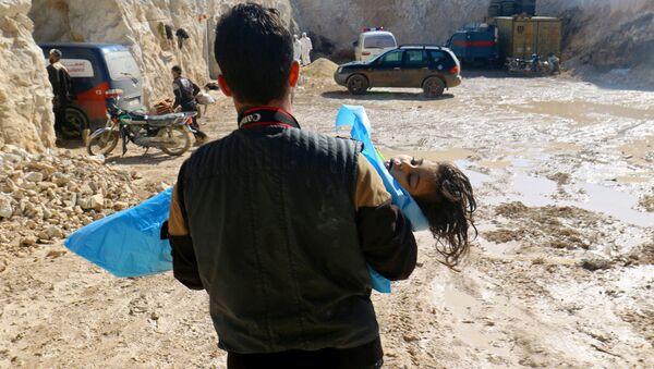 Mężczyzna wynoszący ciało dziewczynki po ataku chemicznym na miejscowość Chan Szajchun - Sputnik Polska