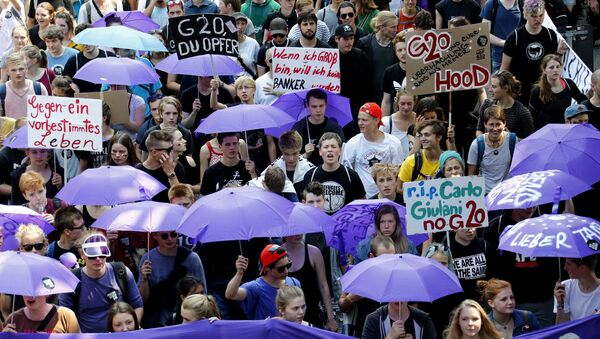 People hold banners and umbrellas as they walk during the protest demonstration at the G20 summit in Hamburg, Germany, July 7, 2017 - Sputnik Polska