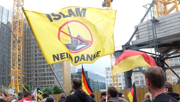 Uczestnicy protestu przeciwko proimigracyjnej polityce kanclerz Niemiec Angeli Merkel w Berlinie - Sputnik Polska