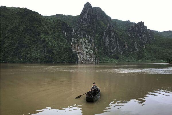 Człowiek w łodzi na jeziorze Sinpyon, Korea Północna - Sputnik Polska