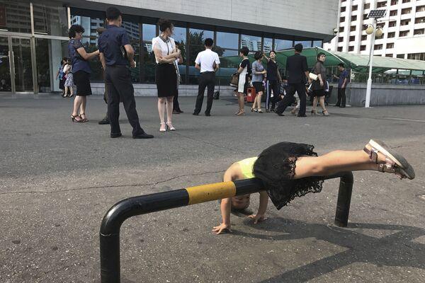 Dziewczynka bawi się na parkingu przy sklepie w Pjongjangu - Sputnik Polska