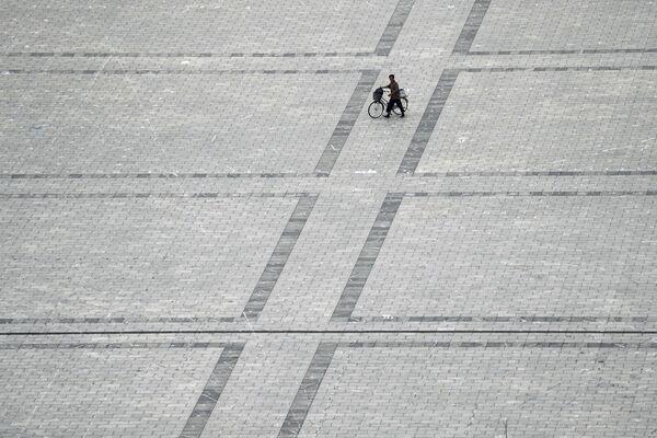 Mężczyzna z rowerem na pustym placu Kim Ir Sena - Sputnik Polska