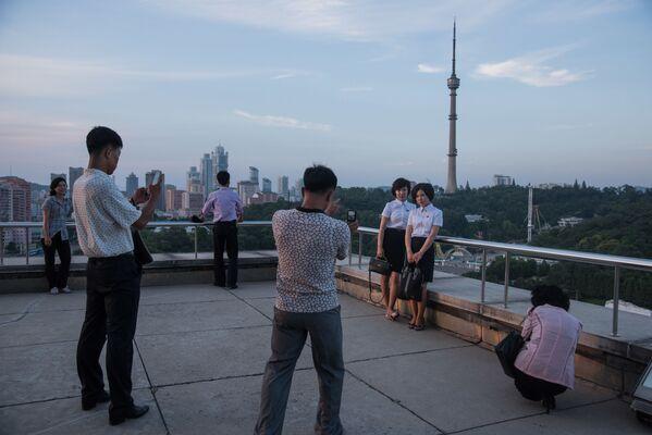 Turyści fotografują się na tle triumfalnej arki w Pjongjangu - Sputnik Polska