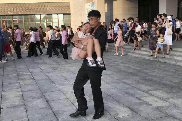 Mężczyzna niesie śpiącą dziewczynkę na rękach po wyjściu z cyrku w Pjongjangu - Sputnik Polska