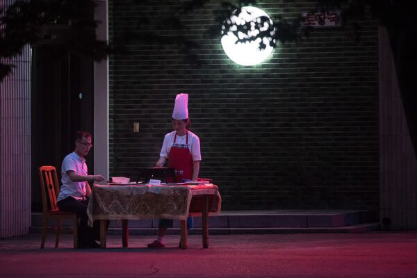 Mężczyzna jędzący na werandzie restauracji w Pjongjangu - Sputnik Polska