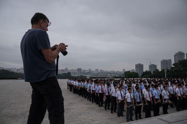 Turysta fotografuje grupę ludzi przy pomniku Kim Ir Sena - Sputnik Polska