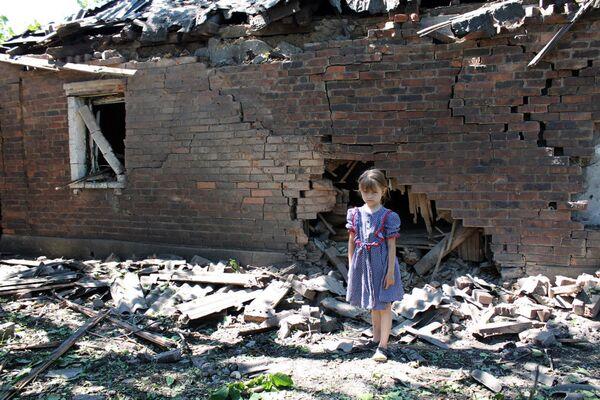 Dziewczynka przy zburzonym domu w Gorłowce - Sputnik Polska