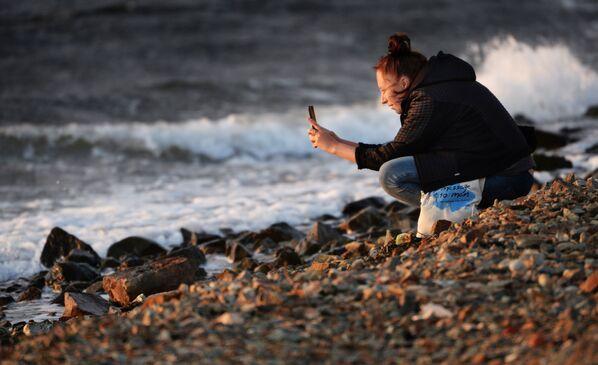 Kobieta robi zdjęcie na brzegu Mierzei Tokariewskiego we Władywostoku. - Sputnik Polska