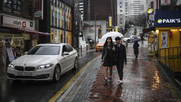 Mieszkańcy miasta z parasolem na jednej z ulic w Seulu - Sputnik Polska