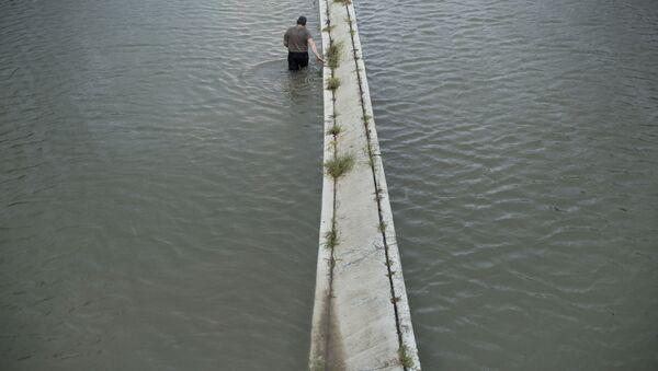 Kierowca sprawdza głębokość zalania na drodze w wyniku huraganu Harvey w stanie Teksas w USA - Sputnik Polska
