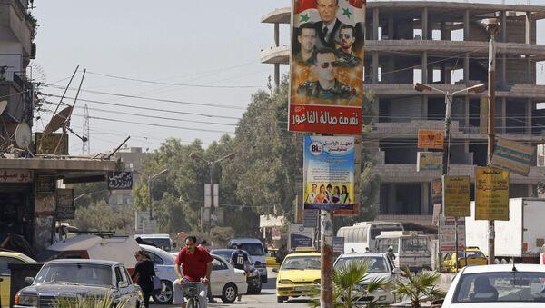 Plakat z wizerunkiem prezydenta Syrii Baszara Asada i jego rodziny na ulicy Damaszku - Sputnik Polska