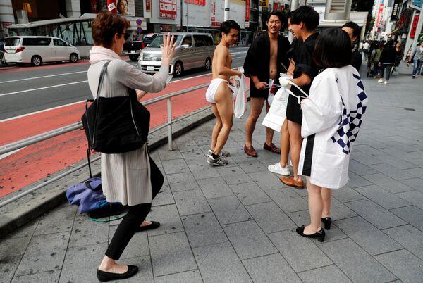 Japończycy ubrani w tradycyjną bieliznę fundoshi podczas akcji sprzątania śmieci na ulicach Tokio - Sputnik Polska