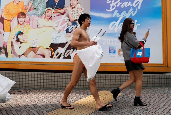 Japończyk ubrany w tradycyjną bieliznę fundoshi podczas akcji sprzątania śmieci na ulicach Tokio - Sputnik Polska