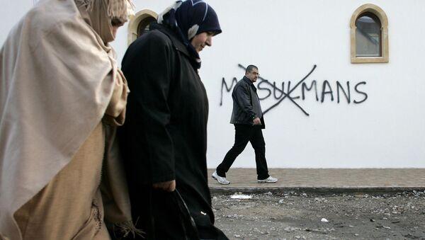 Muzułmanie idący obok ściany z obelgami - Sputnik Polska