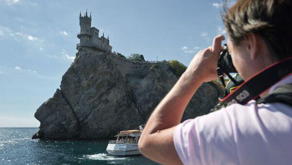 Turysta fotografujący zamek Jaskółcze gniazdo z pokładu motorowca - Sputnik Polska