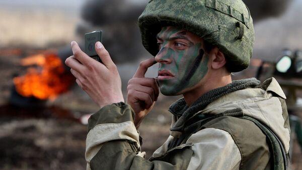 Żołnierz piechoty morskiej nanosi na twarz barwy wojenne przez rozpoczęciem ćwiczeń piechoty morskiej Floty Oceanu Spokojnego w Kraju Nadmorskim - Sputnik Polska