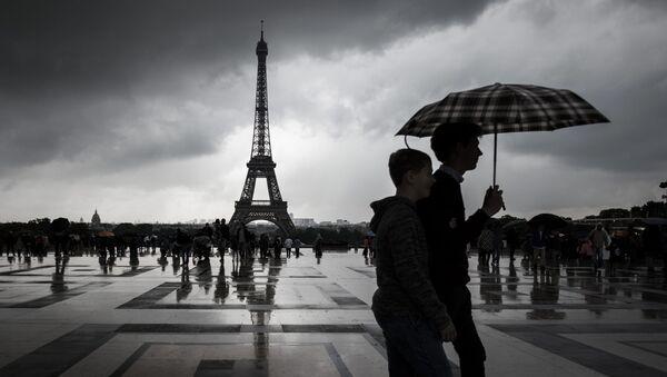 Turyści spacerujące pod parasolem niedaleko wieży Eiffla - Sputnik Polska