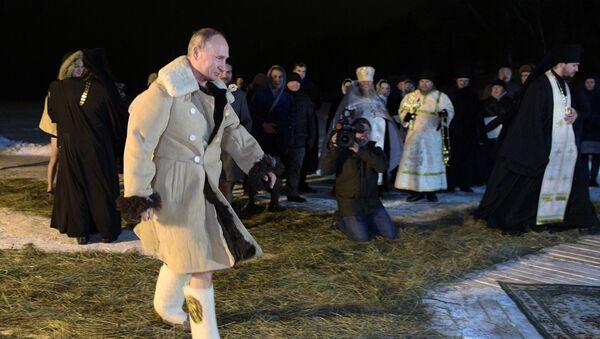 Władimir Putin przed tradycyjną kąpielą w przerębli jeziora Seliger z okazji Święta Chrztu Pańskiego - Sputnik Polska