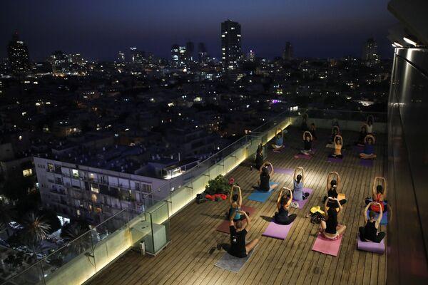 Mieszkańcy Tel Awiwu ćwiczą jogę na dachu jednego z budynków. - Sputnik Polska