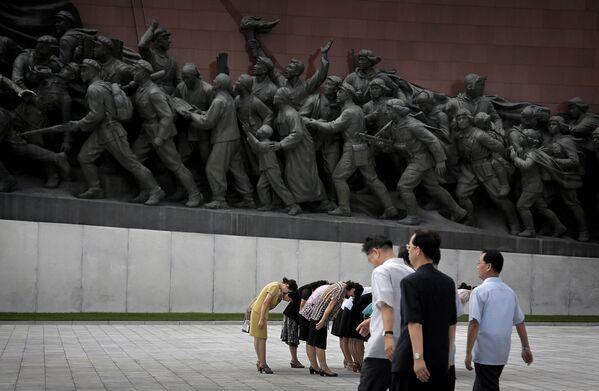 Koreańczycy północni kłaniają się rzeźbom Kim Ir Sena i Kim Dzong Ila - Sputnik Polska