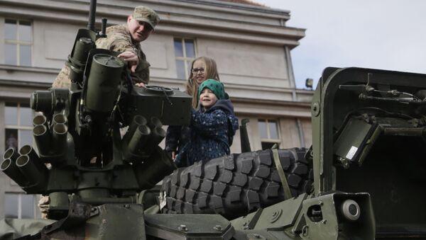 Amerykański żołnierz pokazuje dzieciom wóz opancerzony Stryker w Pradze - Sputnik Polska