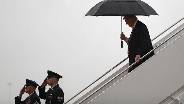 Prezydent USA Donald Trump pod parasolem na lotnisku - Sputnik Polska