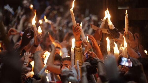Wierni ze świeczkami w czasie zstąpienia Świętego Ognia w Bazylice Grobu Świętego w Jerozolimie - Sputnik Polska