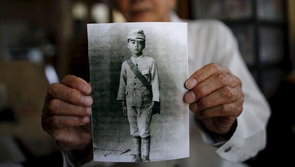 86-letni mieszkaniec prowincji Fukushima Yoshiteru Kohata, który przeżył atak atomowy na Nagasaki, pokazuje swoje szkolne zdjęcie - Sputnik Polska