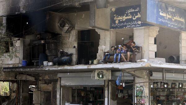 Miezkańcy siedzą na balkonie zburzonego domu w Aleppo - Sputnik Polska