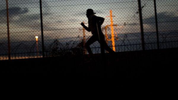 Uchodźca biegnie w kierunku tunelu pod kanałem La Manche w Calais na północy Francji - Sputnik Polska