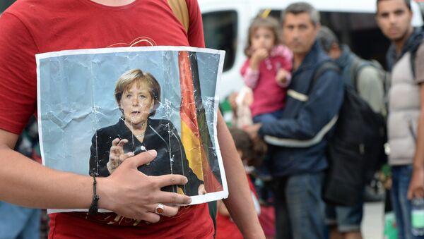 Migranci z portretem Angeli Merkel - Sputnik Polska