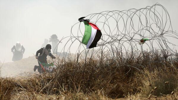 Palestyński demonstrant w czasie starć z izraelskimi siłami bezpieczeństwa przy granicy między Strefą Gazy i Izraelem - Sputnik Polska