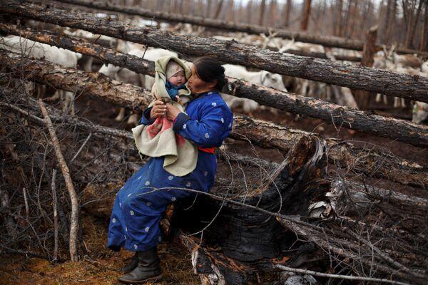 Mongolska kobieta kołysa dziecko na rękach - Sputnik Polska
