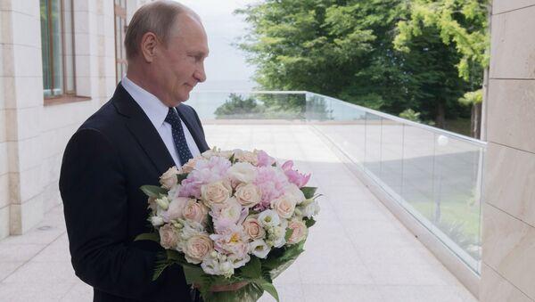 Putin z bukietem kwiatów - Sputnik Polska