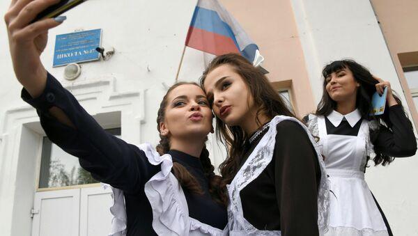 Absolwenci robią sobie selfie przy wejściu do szkoły numer 47 podczas święta zakończenia roku szkolnego w mieście Czita - Sputnik Polska