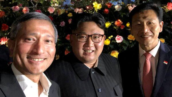 Szef MSZ Singapuru Viviana Balakrishnana zrobił sobie selfie z Kimem i jeszcze jedną osobą, na tle kwiatów - Sputnik Polska