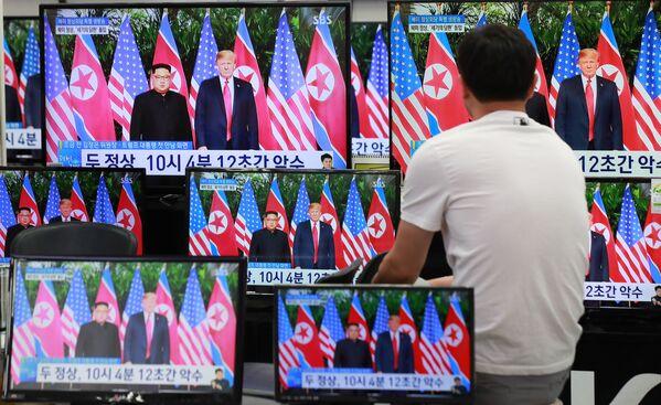 Mieszkaniec Seulu ogląda w telewizji historyczne spotkanie Donalda Trumpa i Kim Dzong Una - Sputnik Polska