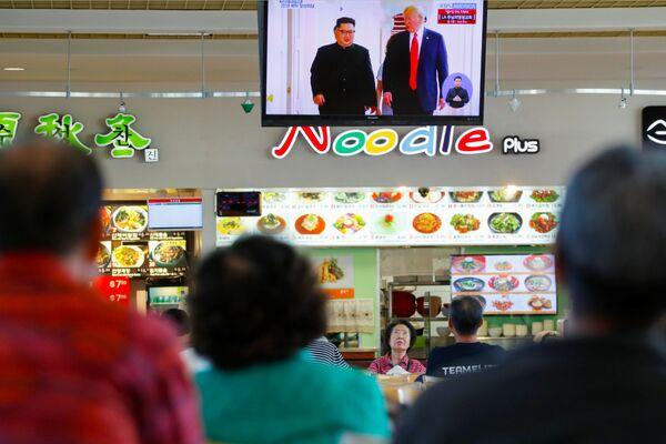 Ludzie oglądają relację ze spotkania Donalda Trumpa i Kim Dzong Una - Sputnik Polska
